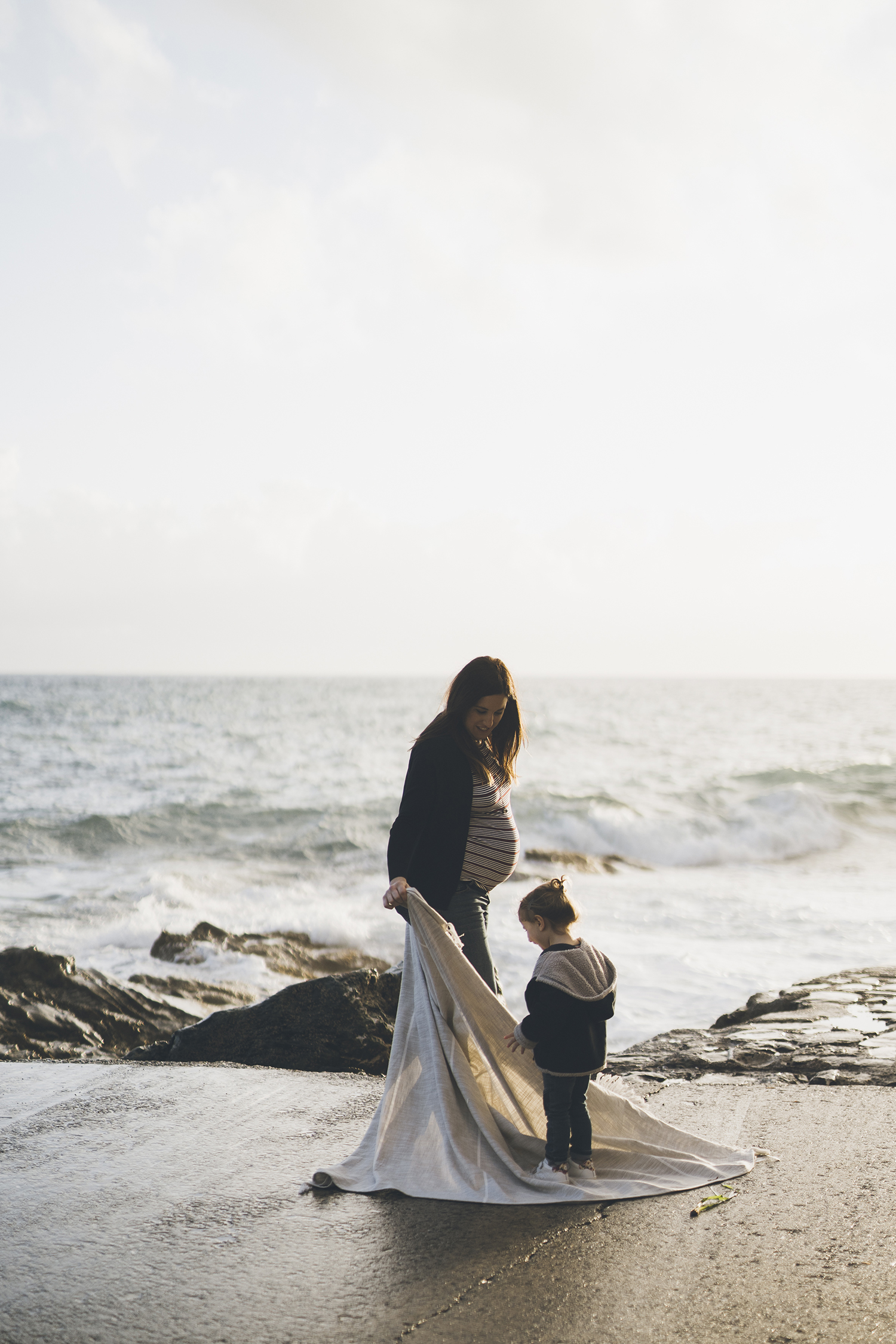 mom and dad playing by the sea. Lifestyle maternity photography.