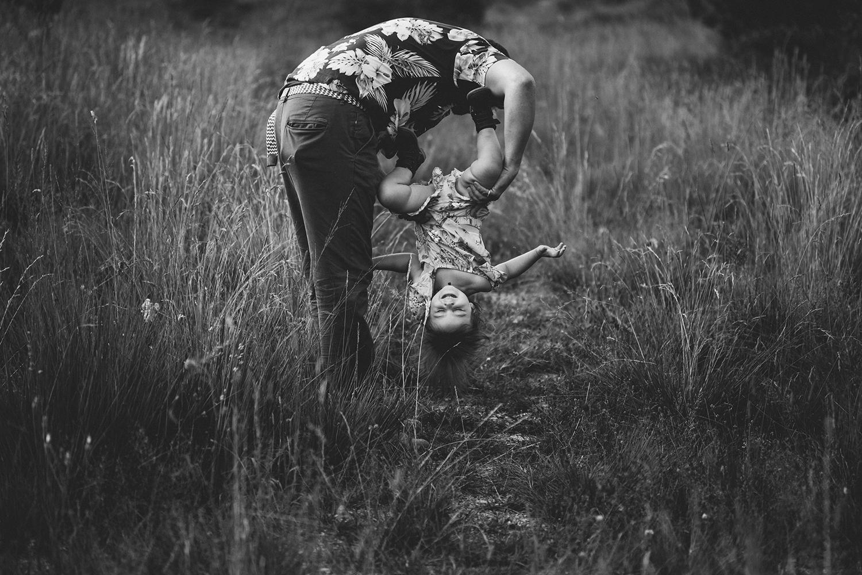 rebecca rinaldi photography. Papà tiene bimba appesa a tesa in giu.