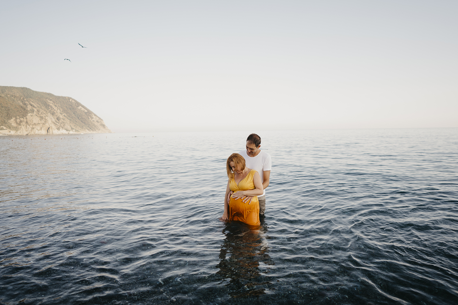 Maternity photographer in Deiva Marina, Italy. Mom coming out of the water. Rebecca Rinaldi Photography. Family lifestyle photographer in Italy.