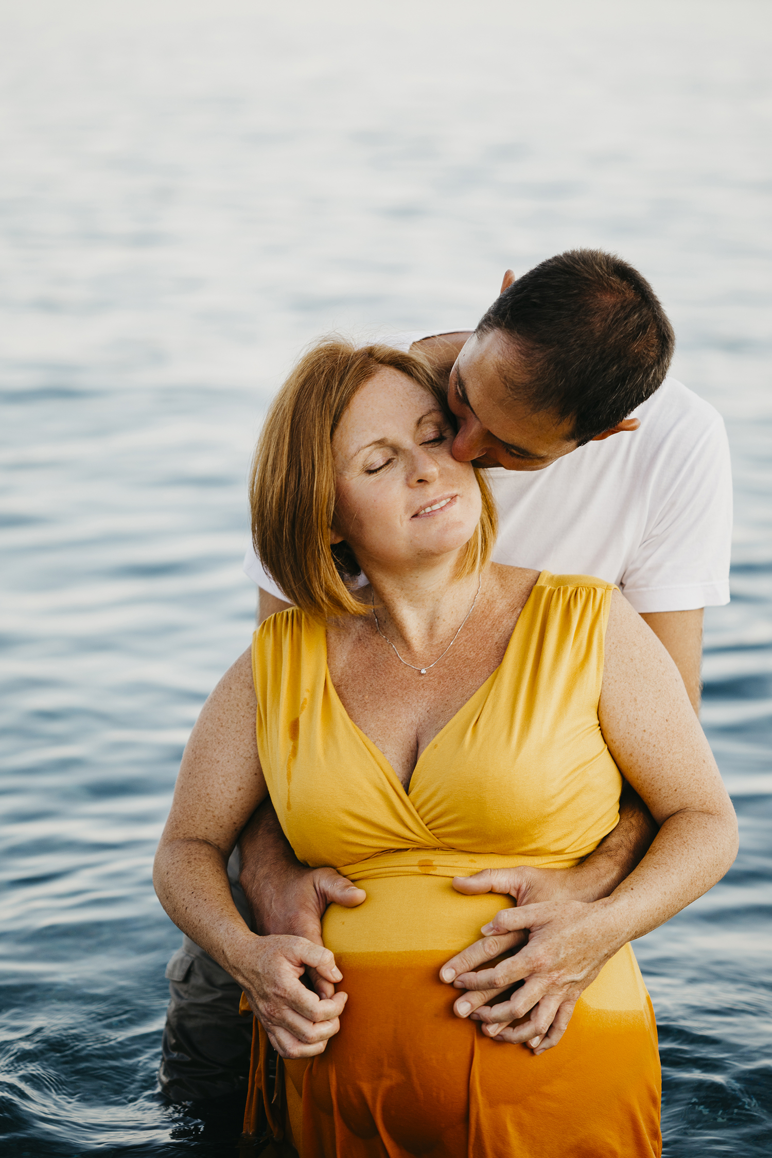 Maternity photographer in Deiva Marina, Italy. Mom and dad kissing in the water. Rebecca Rinaldi Photography. Family lifestyle photographer in Italy.