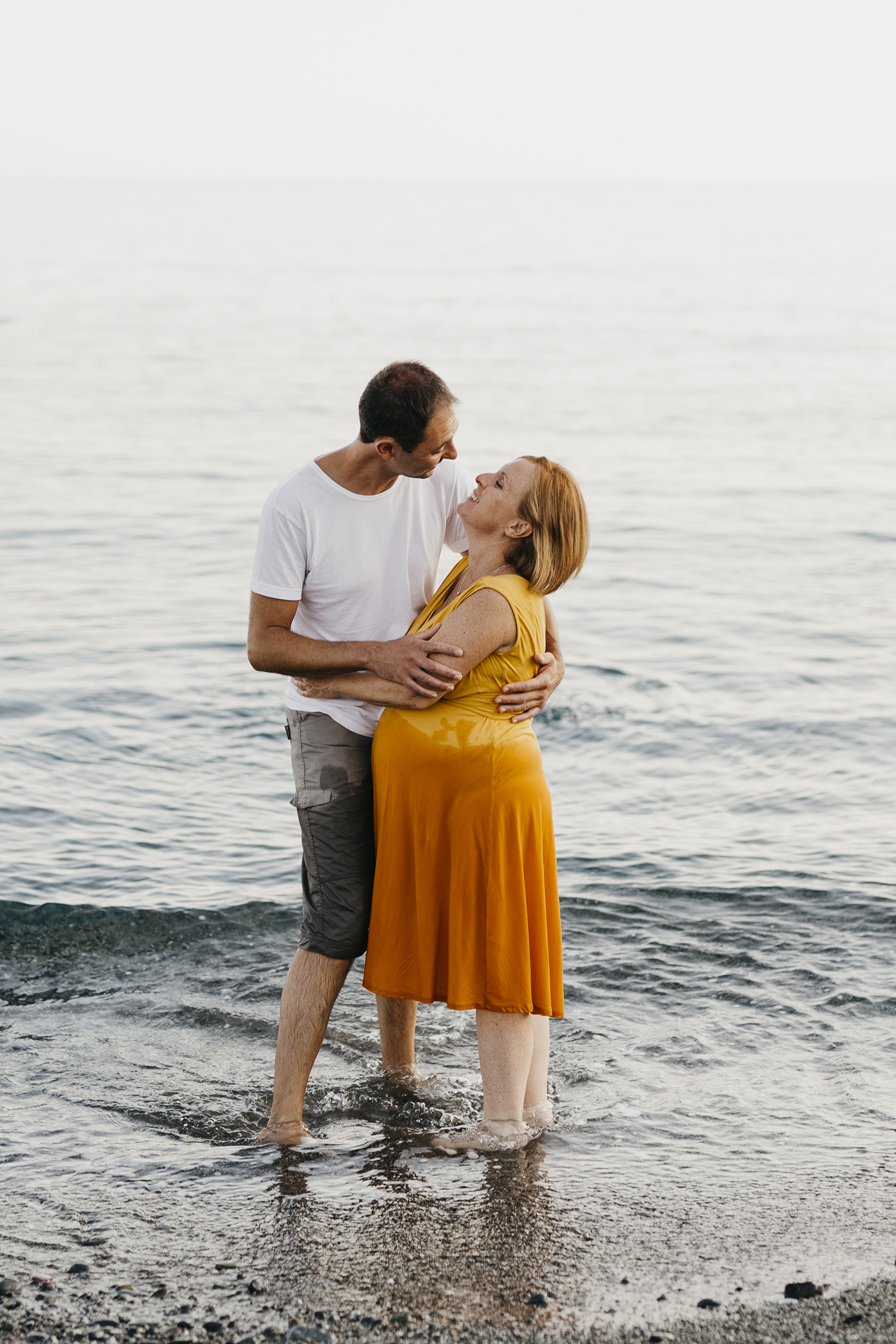 Maternity photographer in Deiva Marina, Italy.  Mom and dad kissing out of  the water. Rebecca Rinaldi Photography. Family lifestyle photographer in Italy.