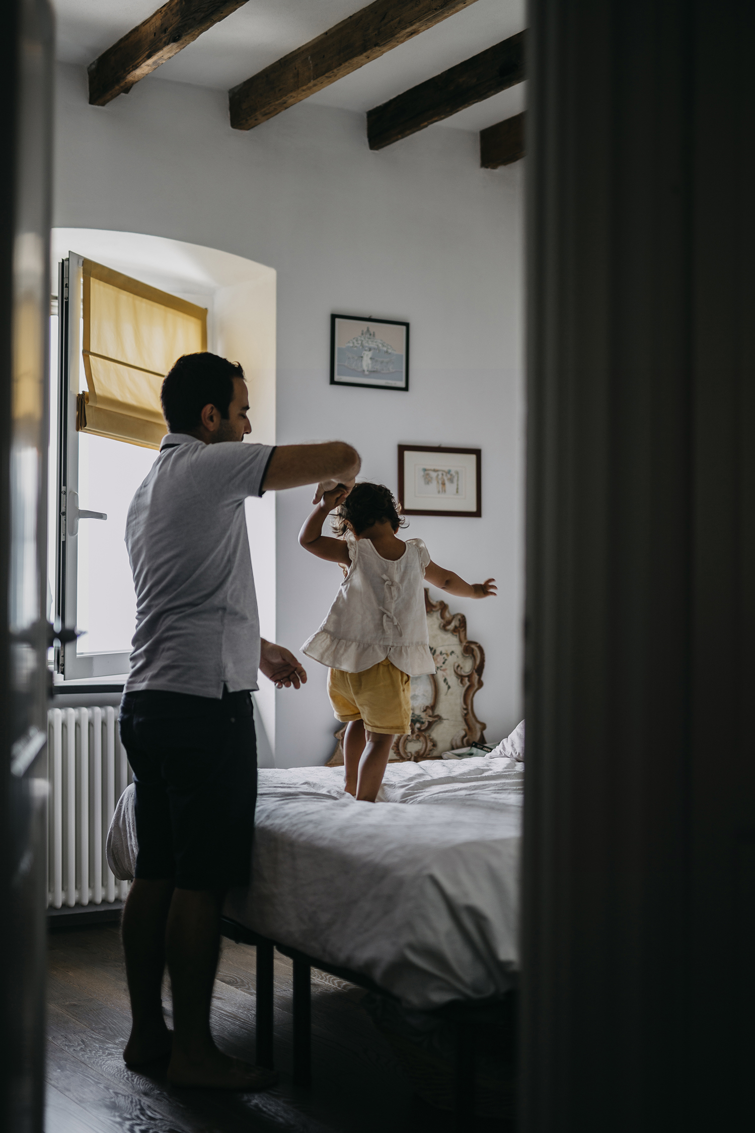 rebecca rinaldi photography. family dad and girl plating on the bed.