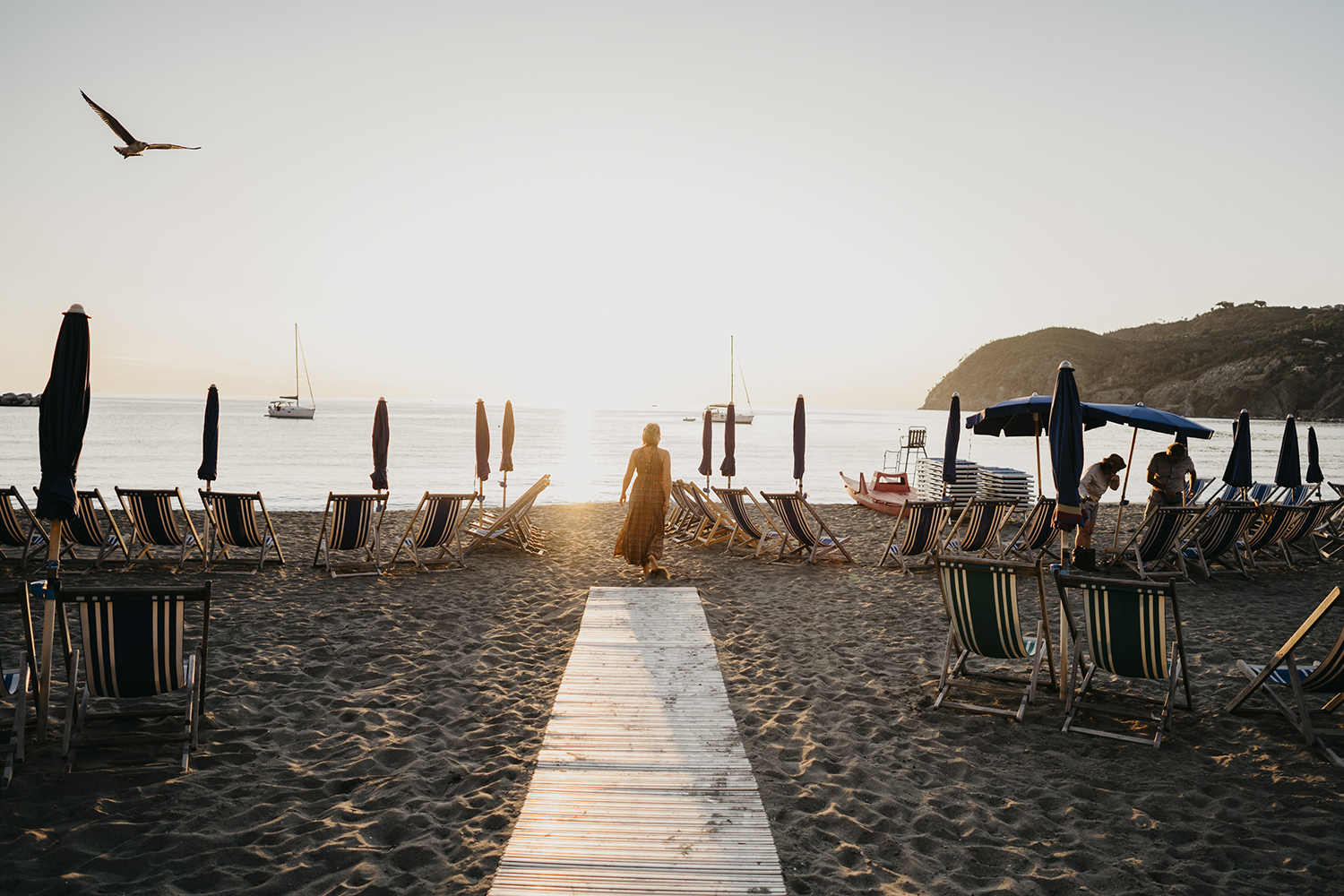 rebecca rinaldi photography. Family photographer in Italy. mom walking on the beach at sunset.