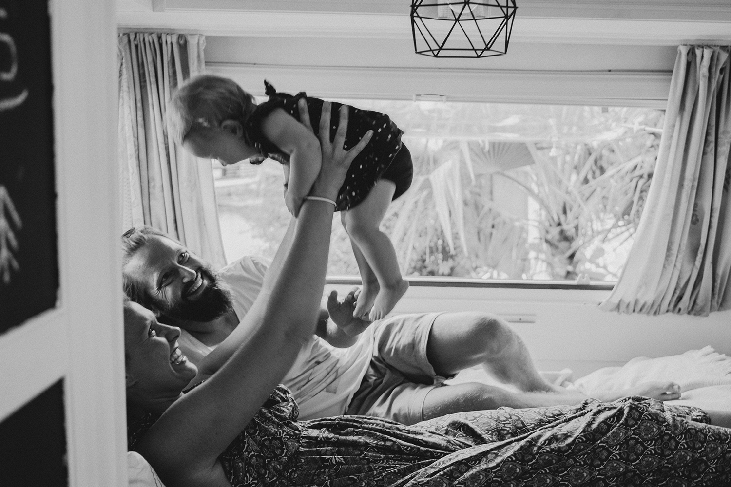 rebecca rinaldi photography. Family photographer in Italy. The family playing in the vintage trailer.