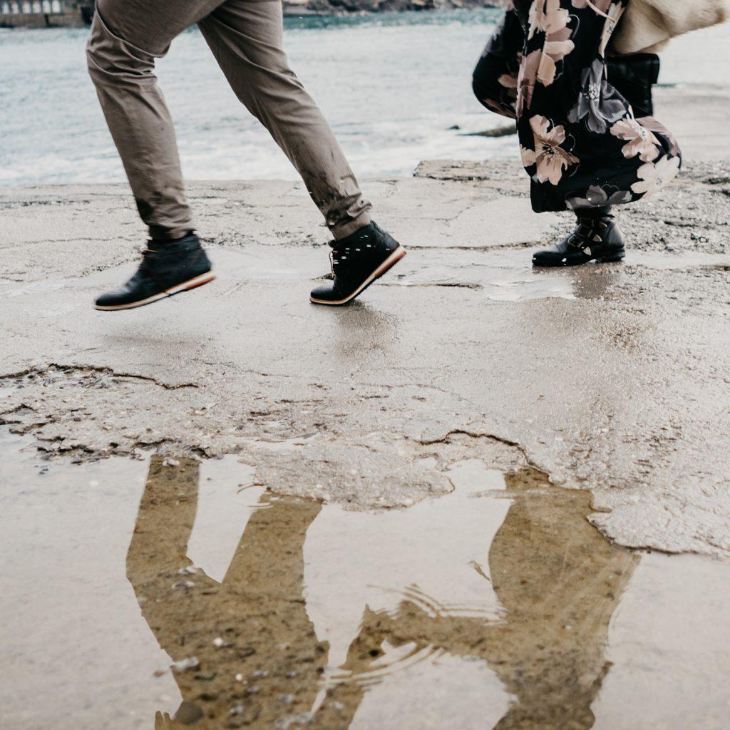 Rebecca Rinaldi fotografia gravidanza e maternità. Servizio fotografico gravidanza a Camogli, Genova. Coppia  passeggia sul molo. dettaglio piedi riflessi in pozzanghera.