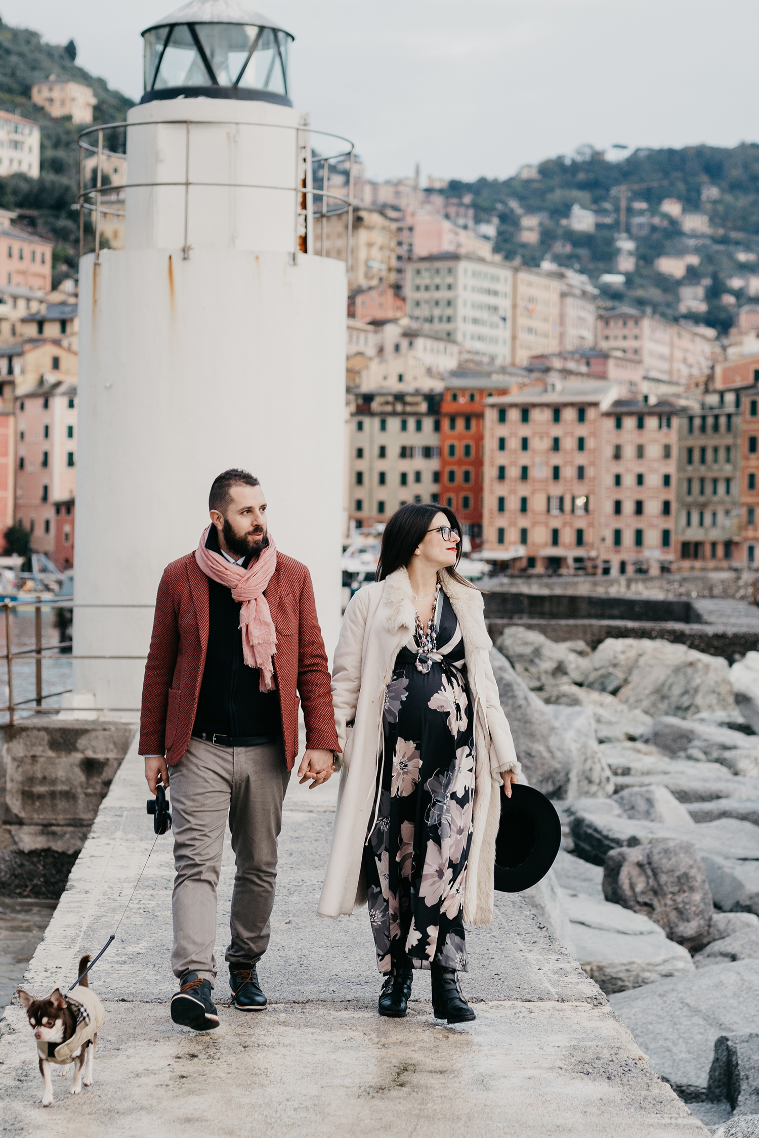 Rebecca Rinaldi maternity photographer in Italy. maternity photo shoot in Camogli, Couple walking  on the peer with chiwawa dog.