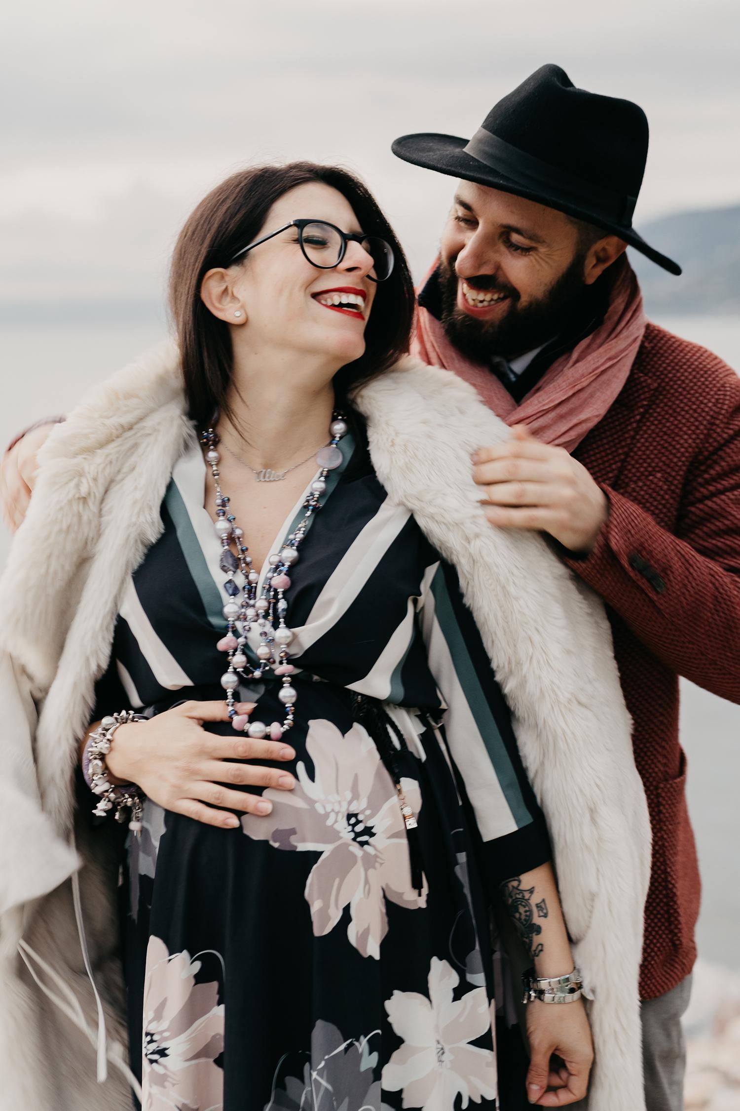 Rebecca Rinaldi fotografia gravidanza e maternità. Servizio fotografico gravidanza a Camogli, Genova. Futuro papà mette cappotto a futura mamma..