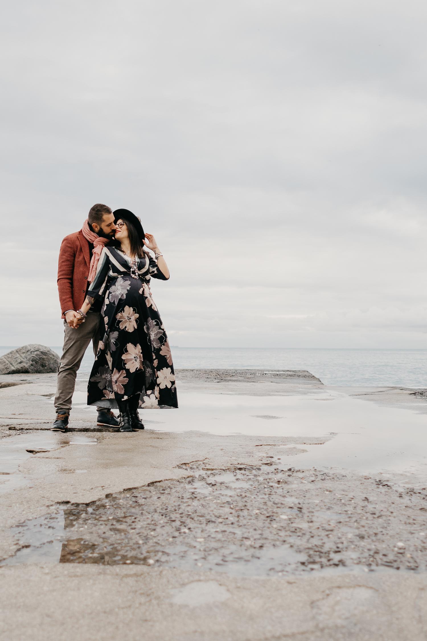 Rebecca Rinaldi fotografia gravidanza e maternità. Servizio fotografico gravidanza a Camogli, Genova. Coppia si bacia sul molo.
