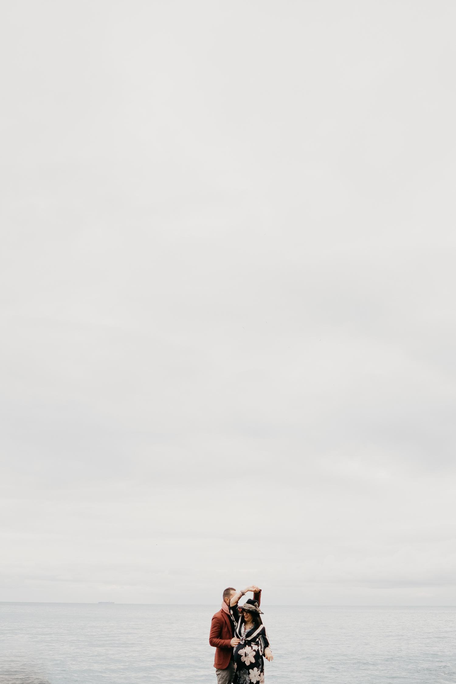 Rebecca Rinaldi fotografia gravidanza e maternità. Servizio fotografico gravidanza a Camogli, Genova. Coppia balla sul molo.