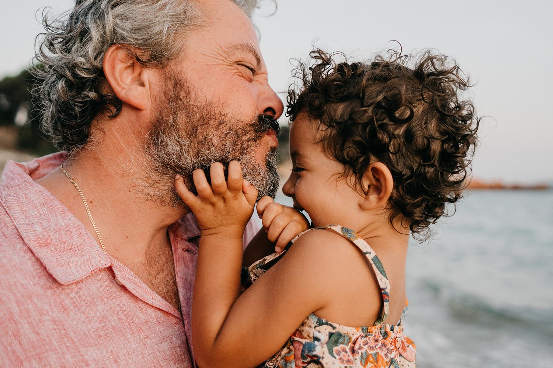 Servizio fotografico reportage di Famiglia. Papà che bacia bimba sulla spiaggia al tramonto.Palombaggia, Santa Giulia, Corsica. by rebecca rinaldi photography