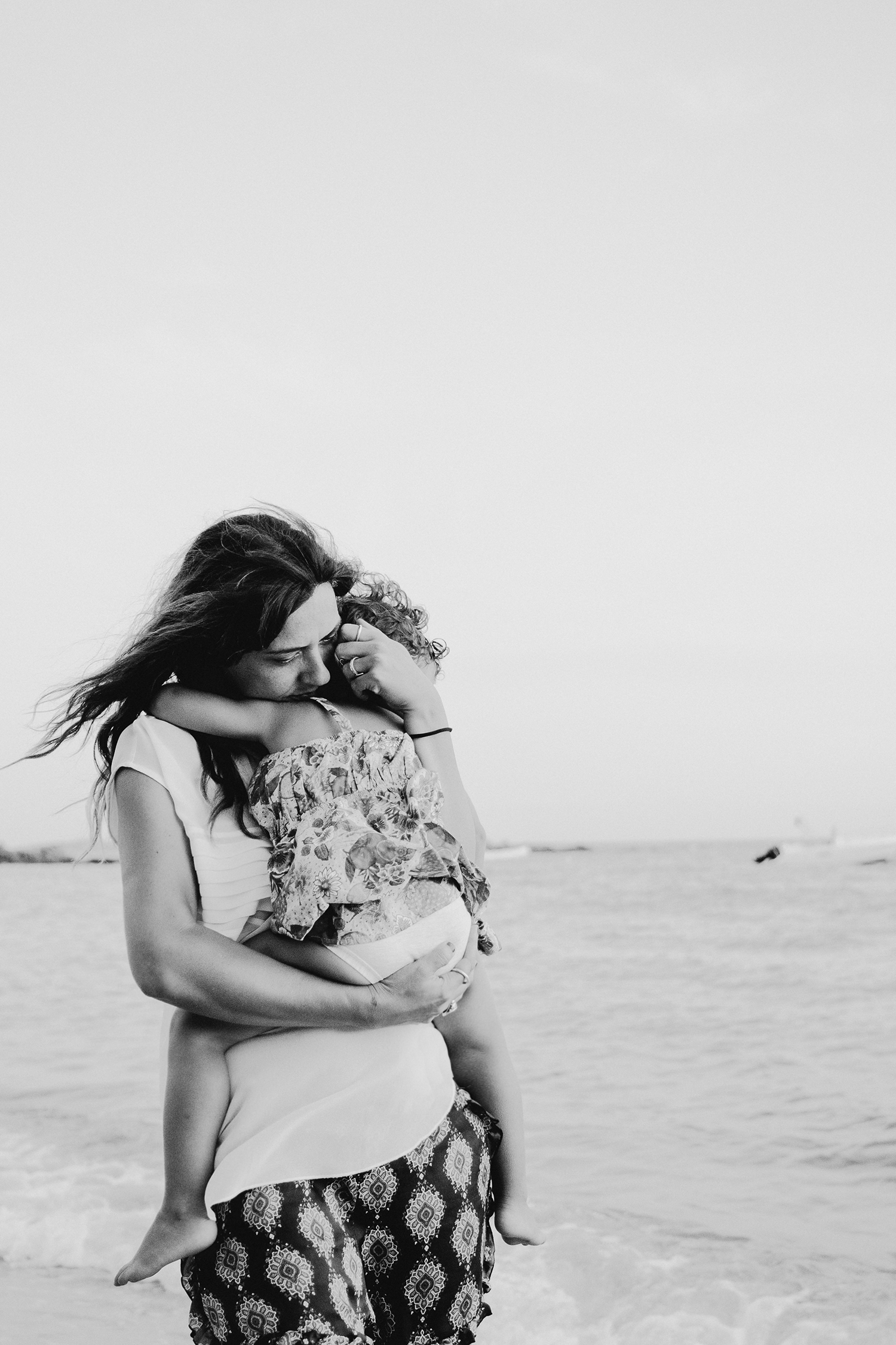 mom hugging daughter playing on the beach during family lifestyle photo session in palombaggia beach, santa giulia. Corsica. by rebecca rinaldi photography