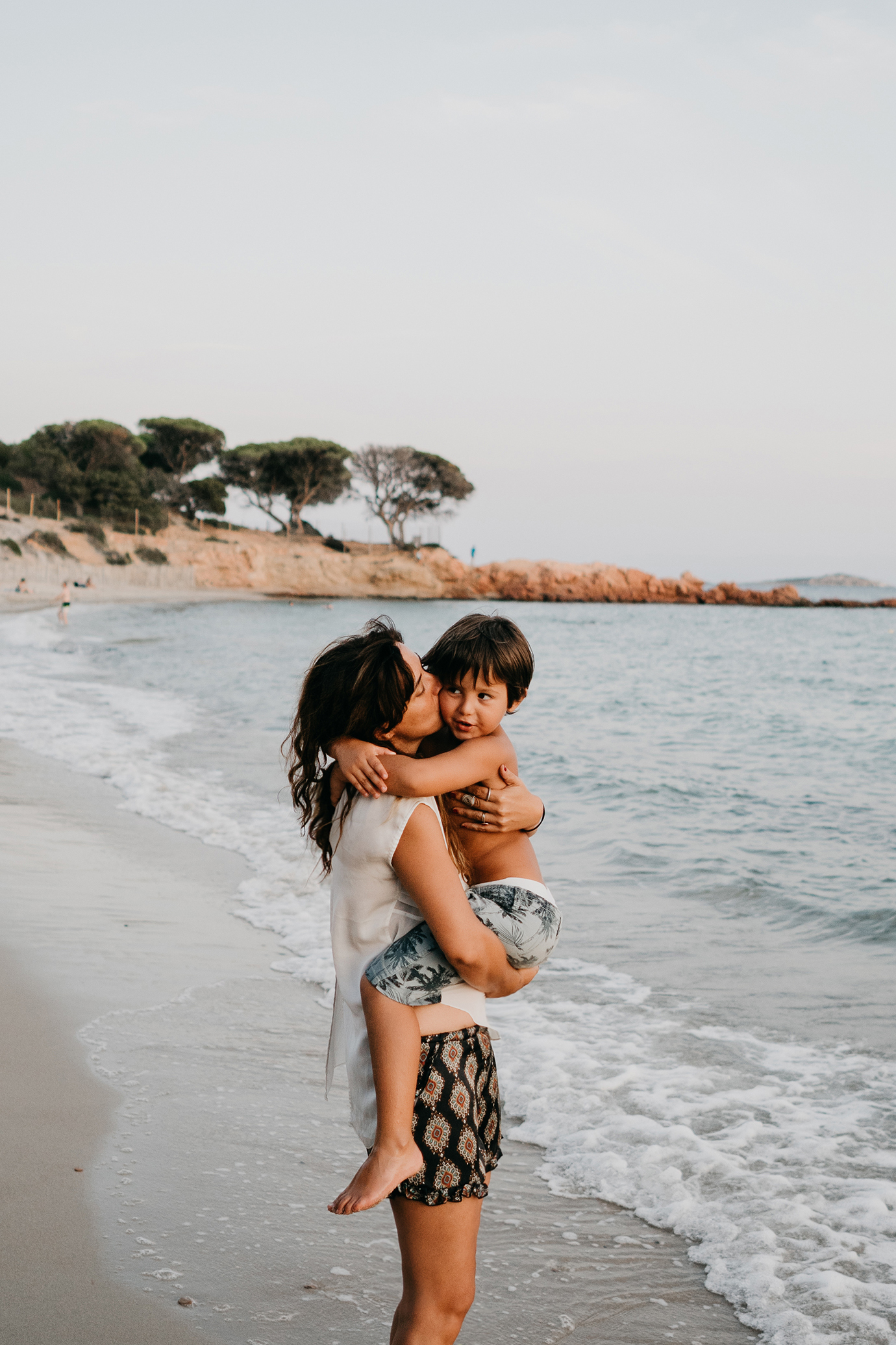 mom hugging kid on the beach during family lifestyle photo session in palombaggia beach, santa giulia. Corsica. by rebecca rinaldi photography