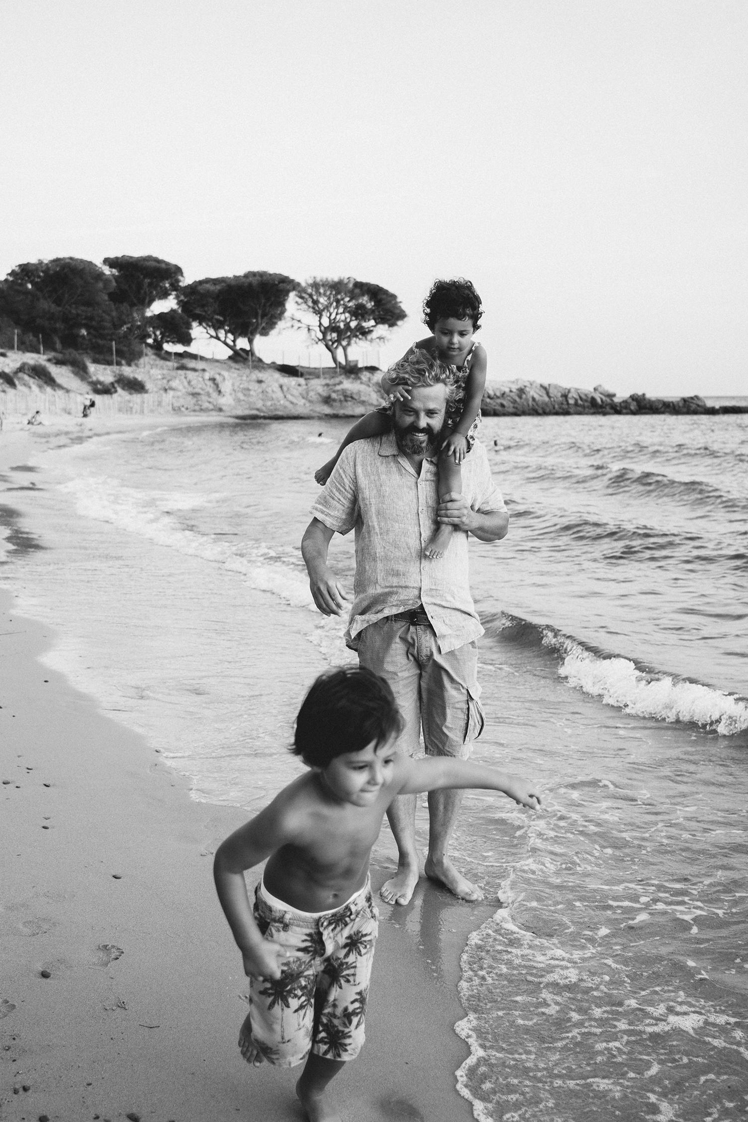 Servizio fotografico reportage di Famiglia.Papà e bimbi che giocano sulla spiaggia al tramonto.Palombaggia, Santa Giulia, Corsica. by rebecca rinaldi photography