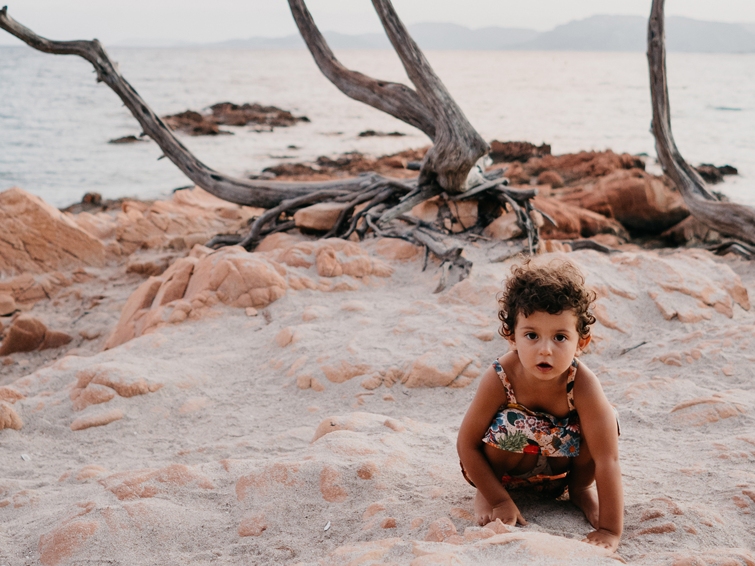 little girl in pink dress on pink rocks during family lifestyle photo session in palombaggia beach, santa giulia. Corsica. by rebecca rinaldi photography