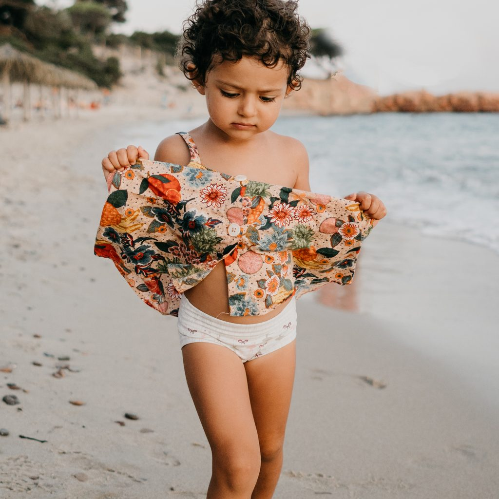 daughter walking on the beach during family lifestyle photo session in palombaggia beach, santa giulia. Corsica. by rebecca rinaldi photography