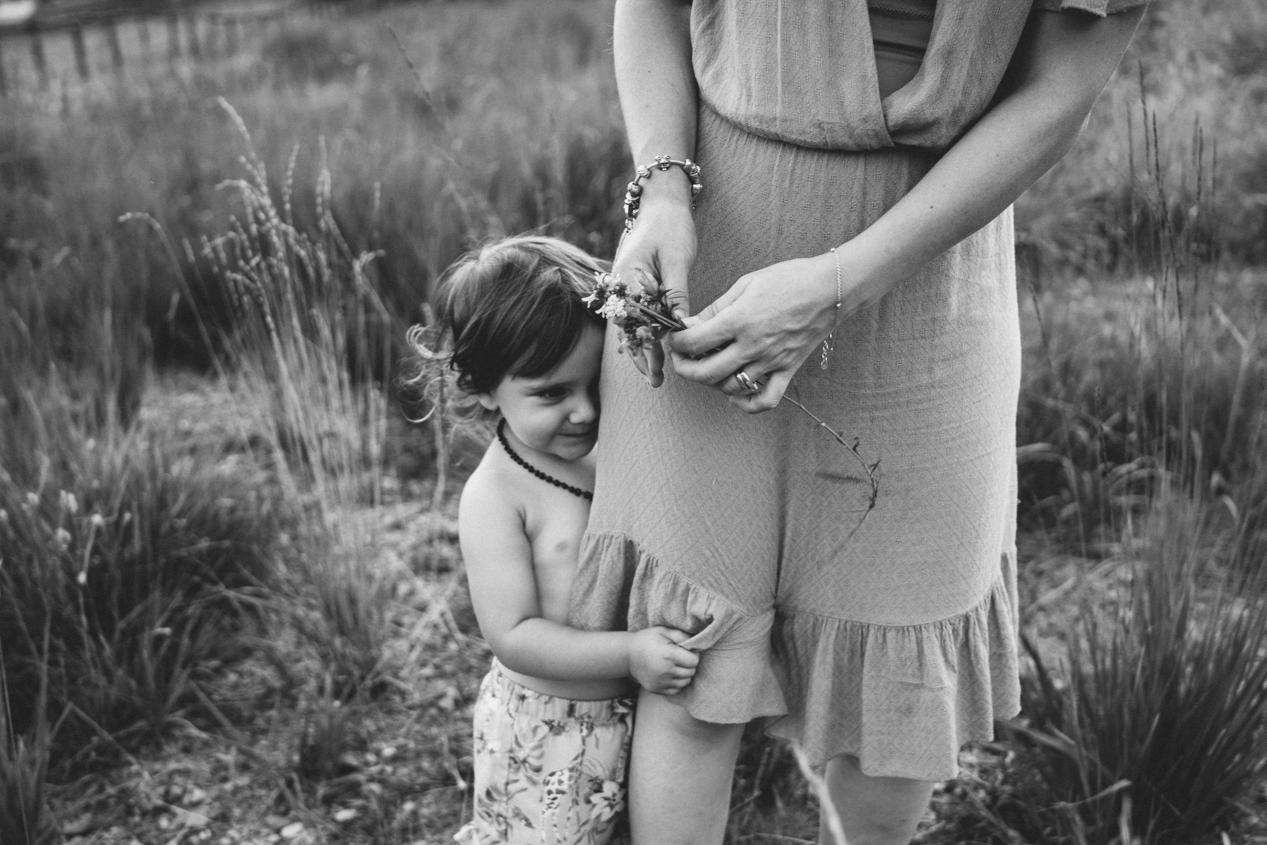 rebecca rinaldi photography. little girl hugging moms leg.