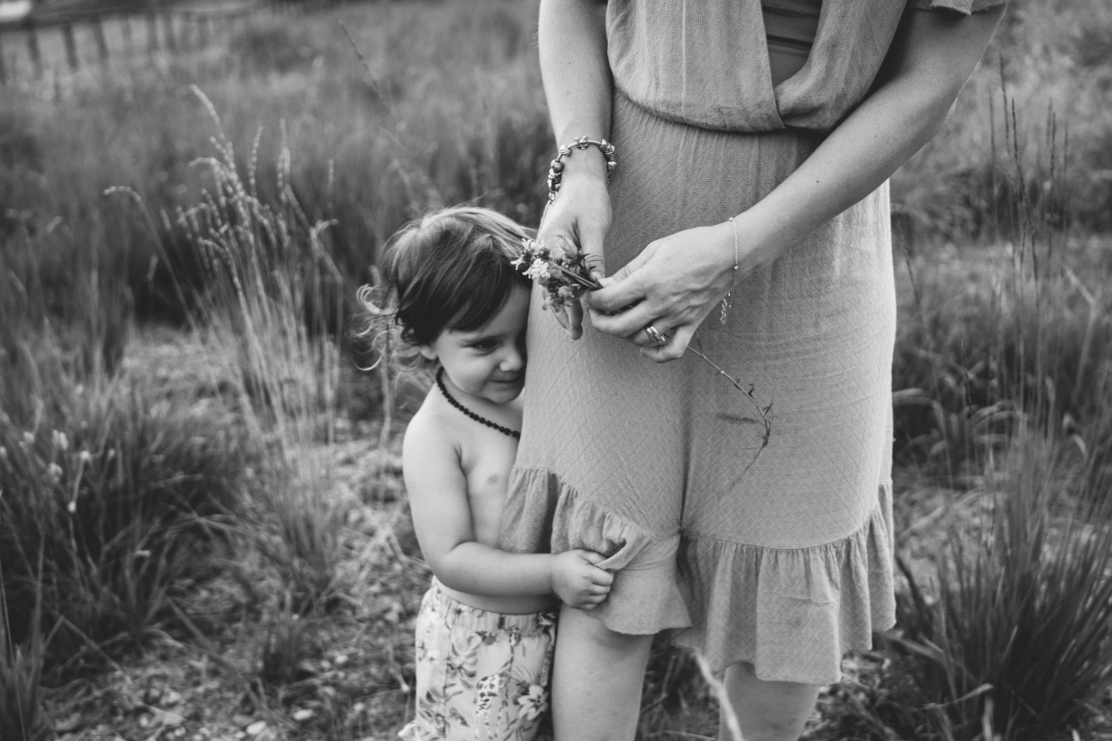 bimba abbraccia gambe della mamma che tiene fiori.