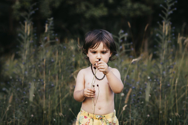 rebecca rinaldi photography. bimba fa gli occhi storti cercando di guardare un bocciolo di un fiorellino