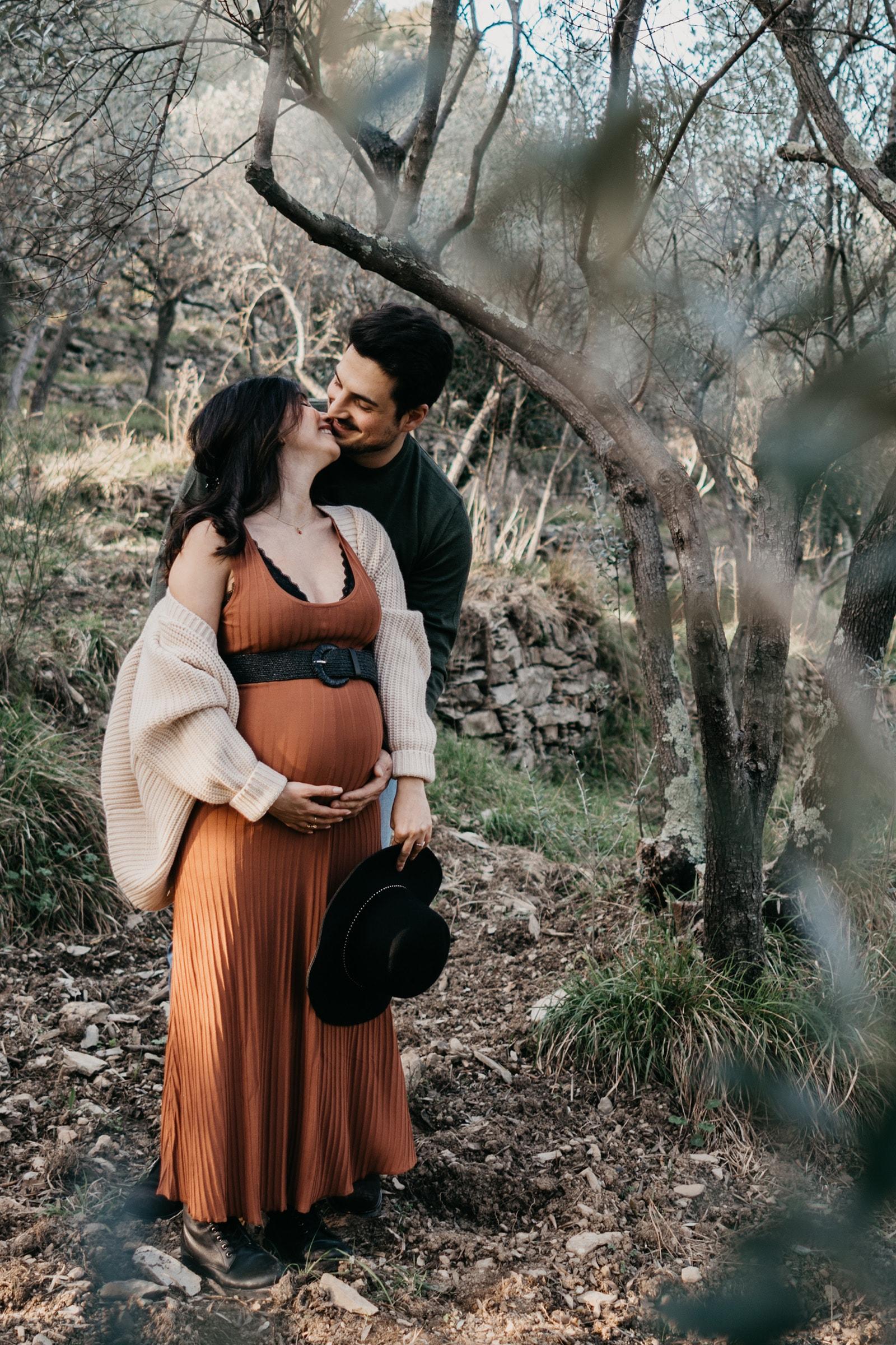 Rebecca Rinaldi fotografia maternità e gravidanza Genova. Futura mamma e futuro papà si baciano sotto agli alberi.