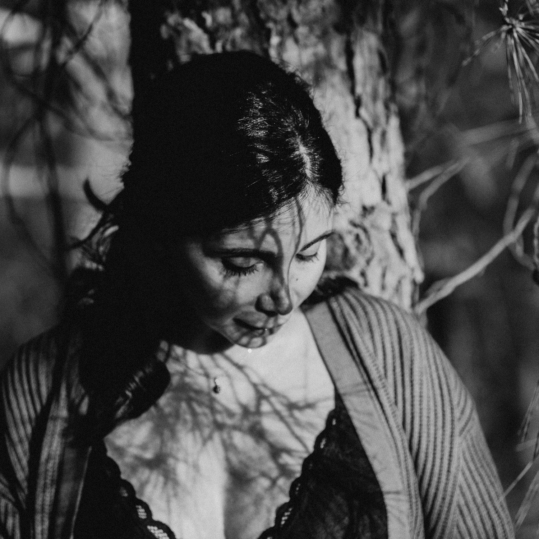 Rebecca Rinaldi fotografia maternità e gravidanza Genova. Futura mamma  accarezza pancione sotto agli alberi, primo piano.