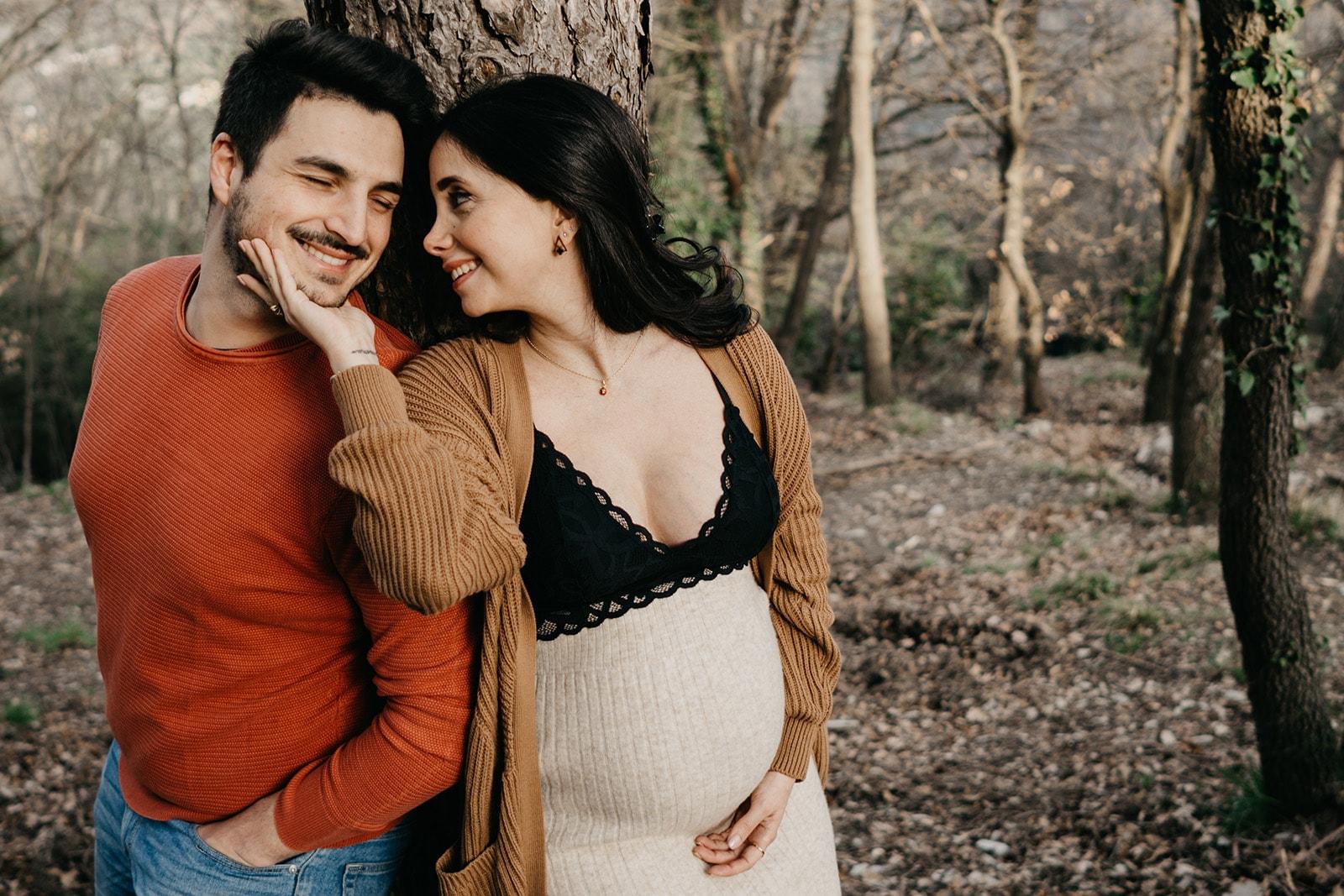 Rebecca Rinaldi fotografia maternità e gravidanza Genova. Futura mamma e futuro papà appoggiati ad un albero si guardano e ridono.