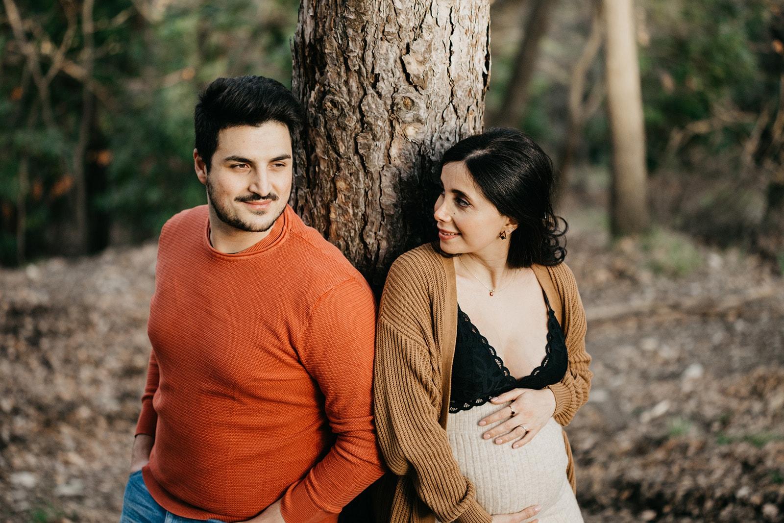 Rebecca Rinaldi fotografia maternità e gravidanza Genova. Futura mamma e futuro papà appoggiati ad un albero si guardano.